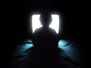 sillhoute of kid child boy watching television close to screen eerie