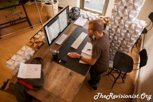 man standing slightly slouching over a standing desk looking at apple monitor