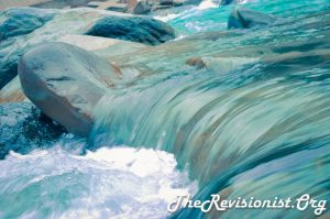 rapid torrent of water passing over grey rocks boulders, with a mini waterfall