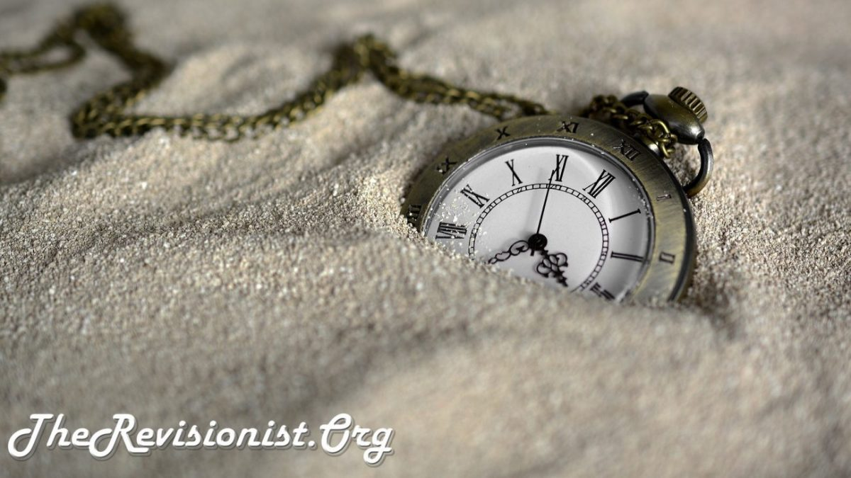 bronze pocket watch inside of sand